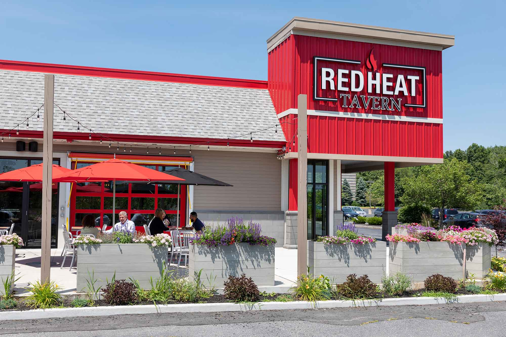 Front exterior of Red Heat Tavern Westborough with patio seating and flower planters